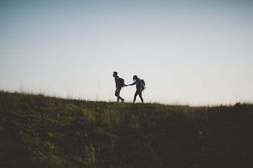 walking couple walking on hill while holding during daytime lantau island