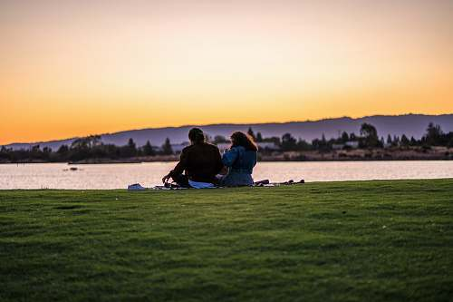 people man and woman sitting on grass while fronting body of water person