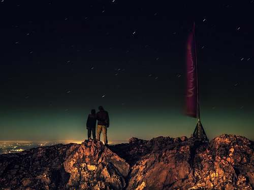 night silhouette of two people standing on brown rocks under starry night stars