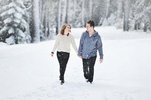 human couple walking on snow near trees during daytime person