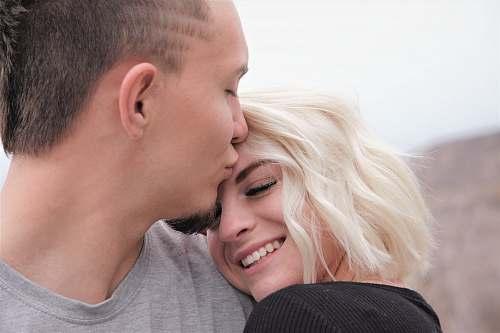 person man kissing woman's forehead kissing