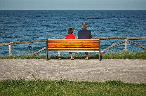 human two person sitting on bench beside body of water person