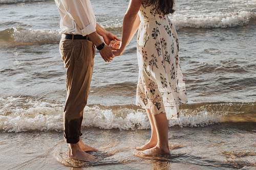 human woman holding hands in front of man standing on seashore person