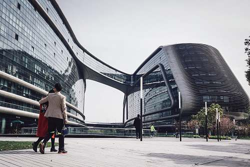 human architectural photography of glass windows of conjoined building walking