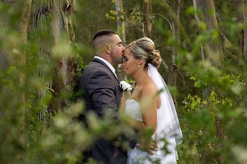 people kissing groom and bride during daytime wedding