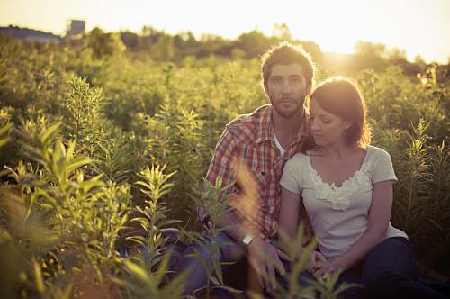 plant man and woman sitting on grass field at daytime human