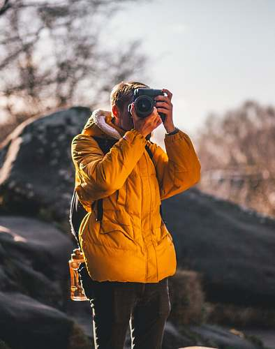 human man taking picture near gray rock people