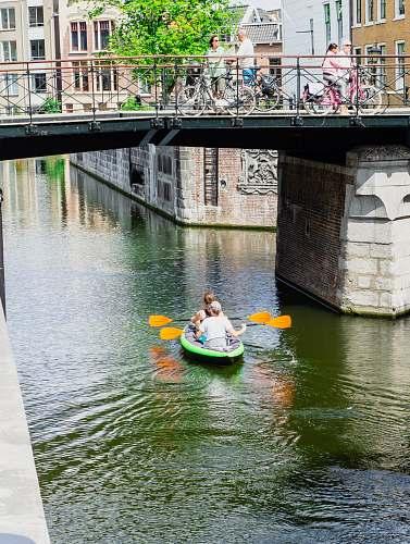 water two people kayaking under bridge boat