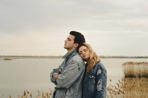 human woman in blue denim jacket leaning on man's shoulder near body of water people