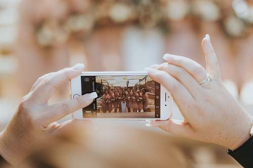 iphone person holding iPhone capturing group of women bridal party