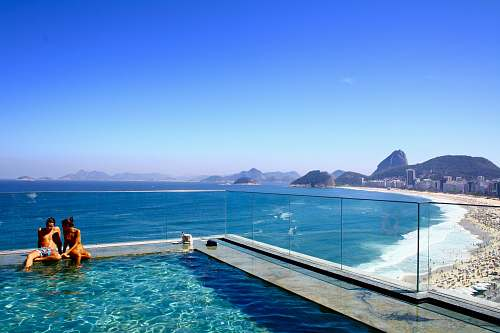 photo rio de janeiro A couple sitting on the edge of a swimming pool overlooking a crowded beach and a deep blue sea water free for commercial use images