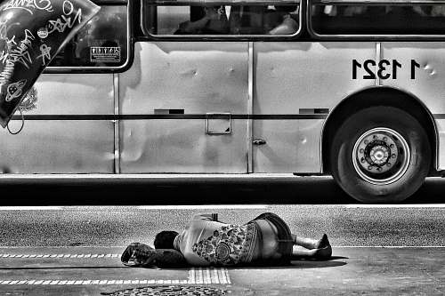black-and-white grayscale photography of person laying on ground near bus shoe