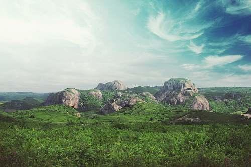 landscape rocks surrounded by green field under blu sky rocks