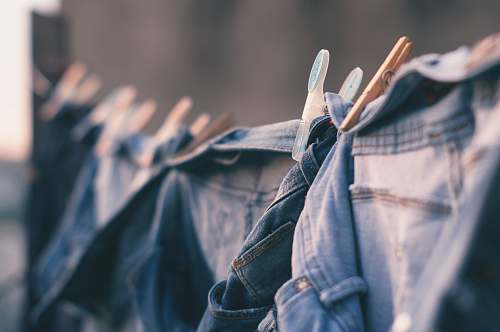 person selective focus photo of blue denim jeans hanged people