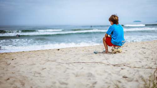 water boy sitting on ball while staring at the ocean beach