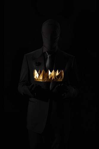 clothing person in black suit jacket holding gold crown human