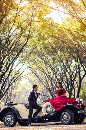 people groom and bride on classic car surrounded by trees person