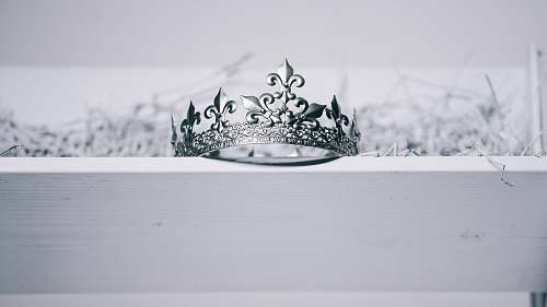 tiara silver-colored crown on top of white wood ornament