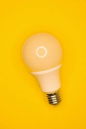 lightbulb white light bulb on yellow surface ascoli piceno