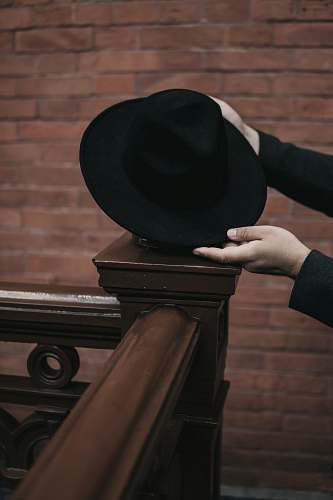 clothing person holding black hat hat