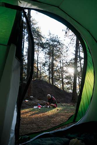 camping man sitting on grass surrounded by trees during daytime tent