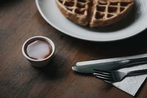 food waffle on plate beside dip, fork, and knife são paulo