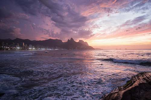 backgrounds white buildings beside seashore behind mountain under thick clouds wallpapers