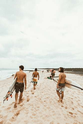 person group of surfer walking on seashore back