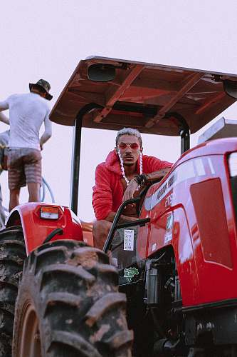 vehicle man riding red tractor tractor