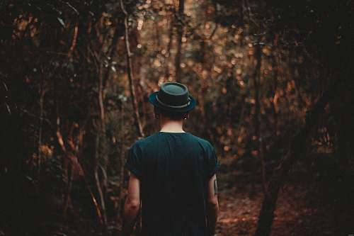 person man wearing black hat walking on forest during daytime people