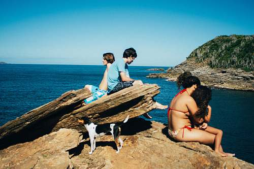 shoreline people sitting near ocean during daytime water