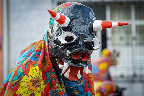 crowd person wearing monster mask covered with yellow and red floral cape festival
