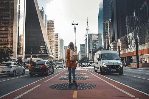 person photography of woman walking in between road with vehicles people