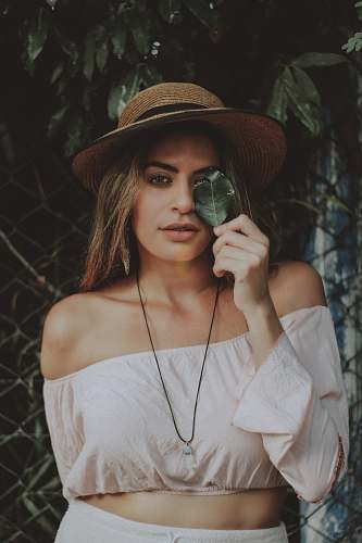 person selective focus photography of women in off-shoulder long-sleeved crop shirt holding leaf covering her one eye people
