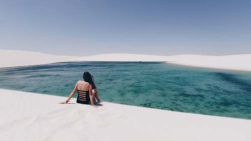 person woman sitting on white sand near body of water people