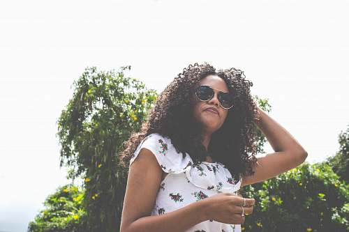 person woman with sunglasses standing near green leafed tree outdoor during daytime people