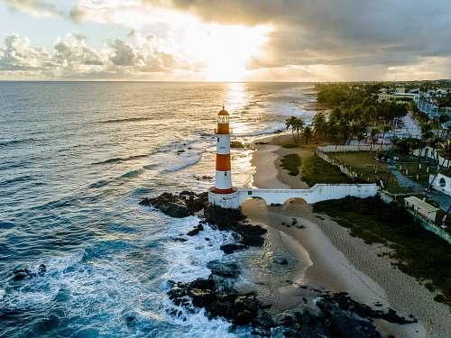 water white and orange lighthouse beside sea sea