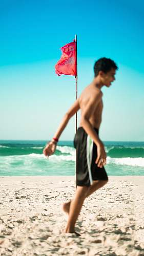 ocean selective focus photo of red flag on brown pole near body of water beach