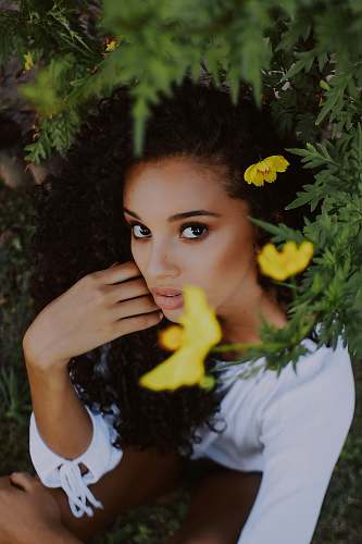 person women's white scoop-neck long-sleeved blouse beside yellow petaled flower plants during daytime human