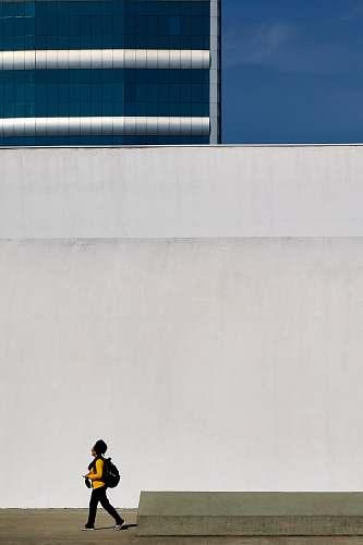 people human in yellow long-sleeved T-shirt walking beside white concrete wall human