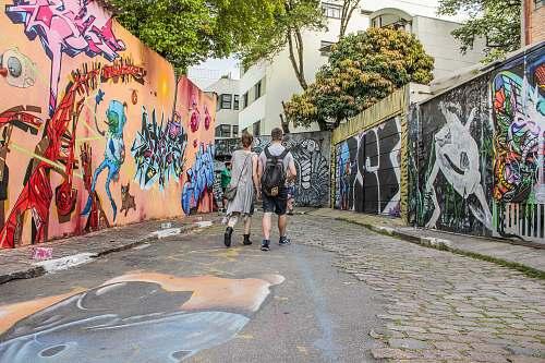 people man and woman standing between wall with graffiti artwork graffiti