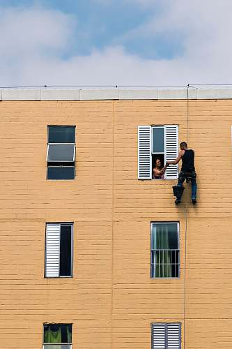 human man hanging on building near woman in window during daytime people