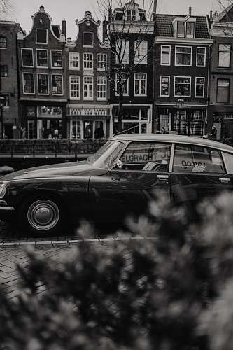 car grayscale photo of classic car parked near building automobile