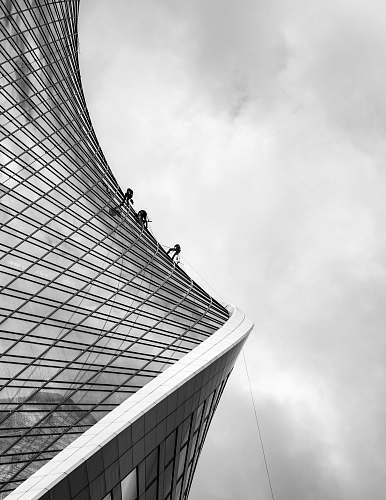 building grayscale photo of men climbing on building office building