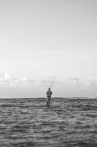 human grayscale photo of person fishing on sea outdoors