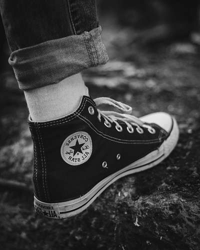 apparel grayscale photography of person in Converse high-tops clothing
