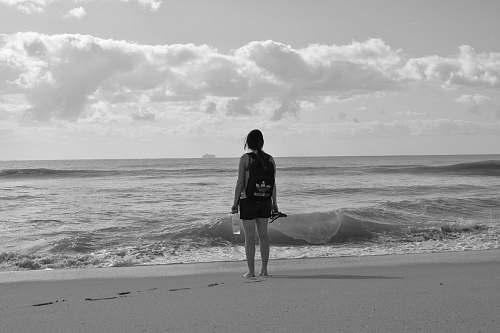 clothing woman standing near seashore facing back shorts