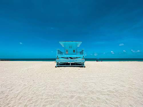 water blue and white lifeguard house on beach during daytime sea