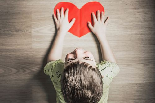 photo boy in green shirt holding red paper heart cutout on brown table free for commercial use images