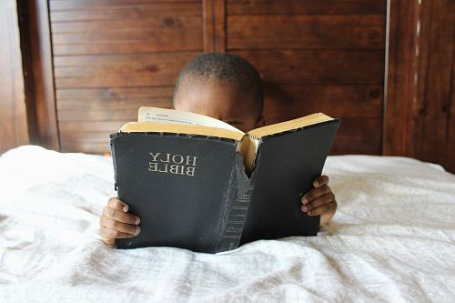 photo boy reading Holy Bible while lying on bed free for commercial use images